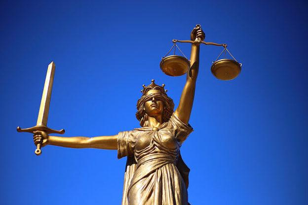 En contre-plongé, une statue de la Justice, yeux bandés, portant une balance dans la main gauche et un glaive dans la main droite.