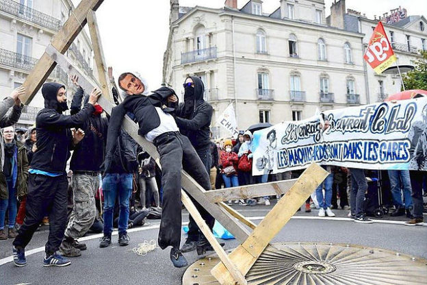 Des manifestants, sur une place, attachent un mannequin portant un masque d'Emmanuel Macron à une potence.