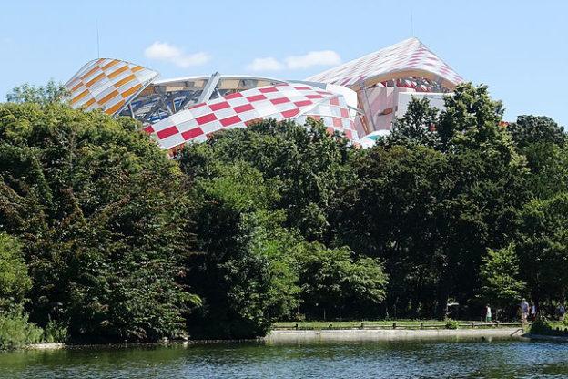 Une architecture étrange barriolée de damiers blanc et rouge émerge derrière un bois au bord de l'eau