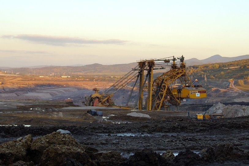 Une grande structure extrait des terres rares du sol dans un paysage désolé.