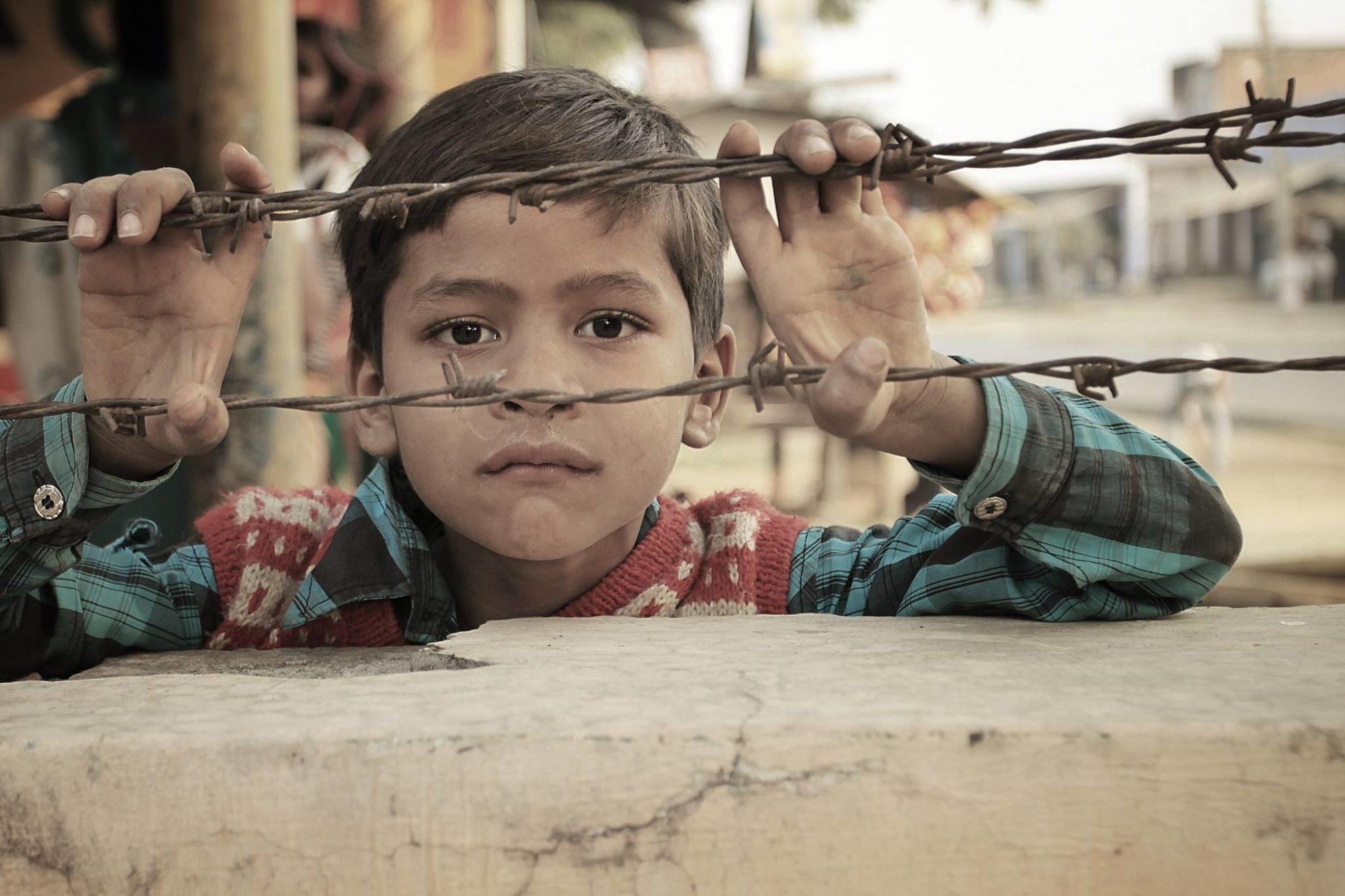 Enfant derrière les barbelés d'un camp de réfugiés