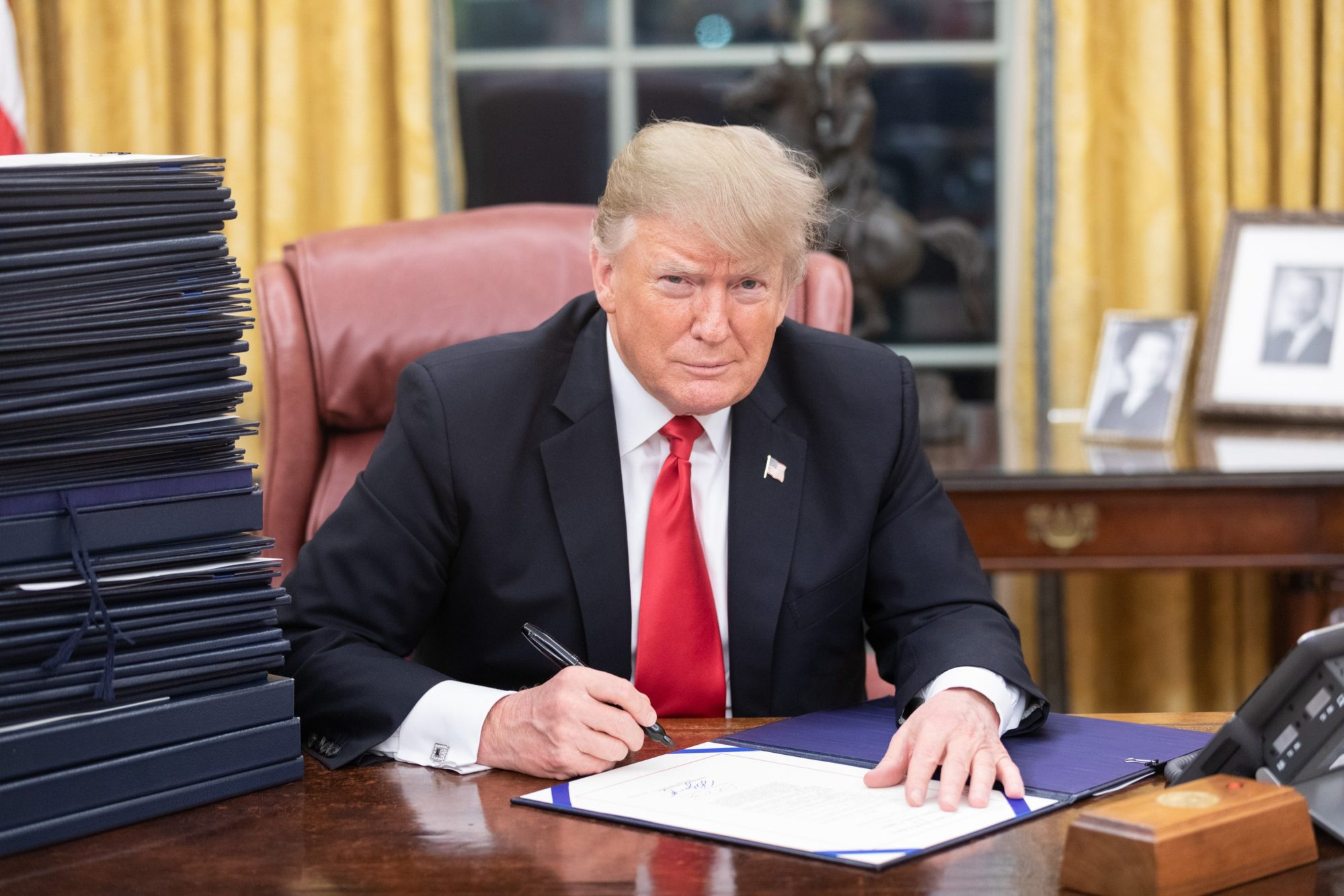 Donald Trump signing in the oval office