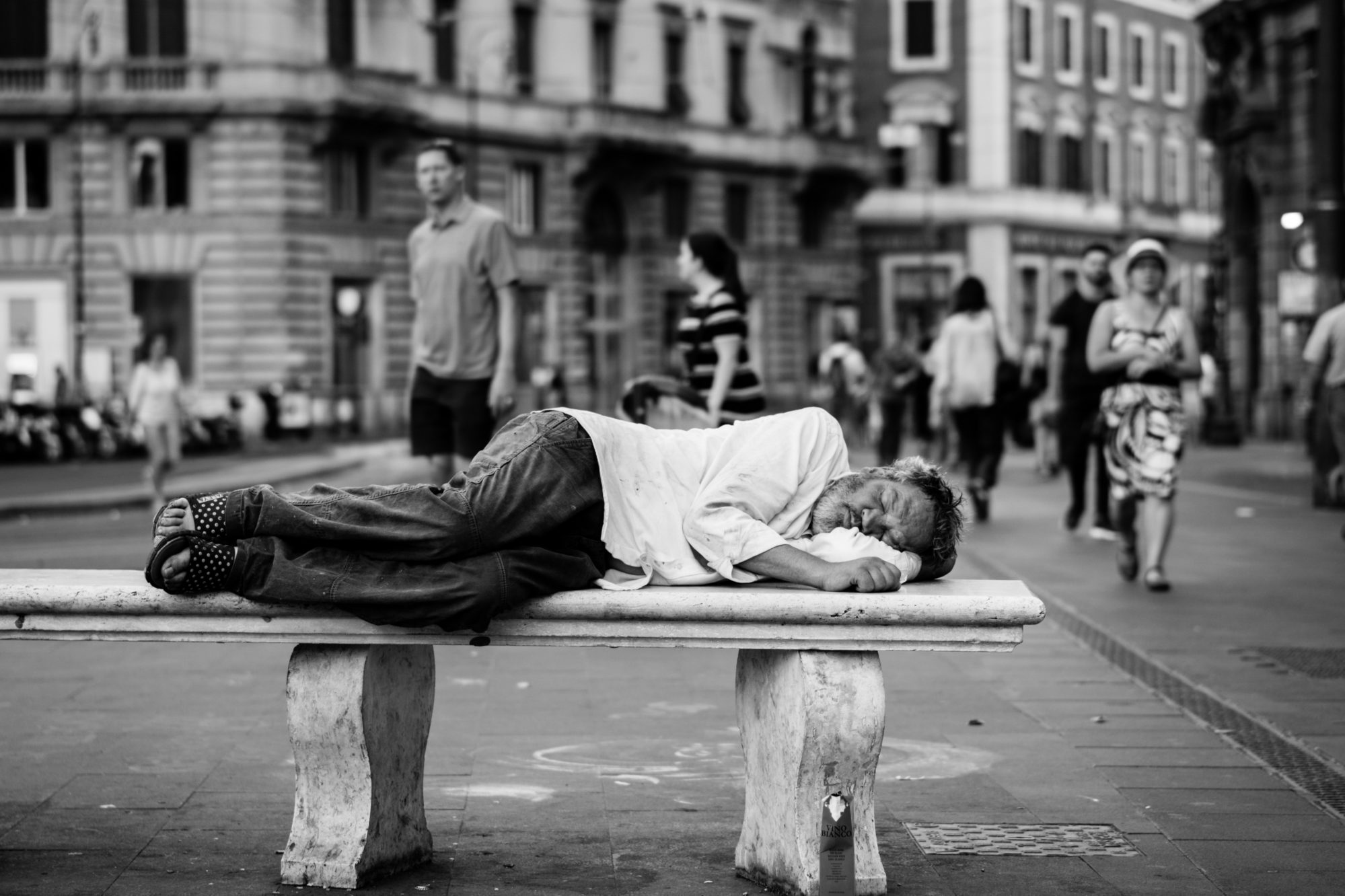 Homme défavorisé dormant sur un banc
